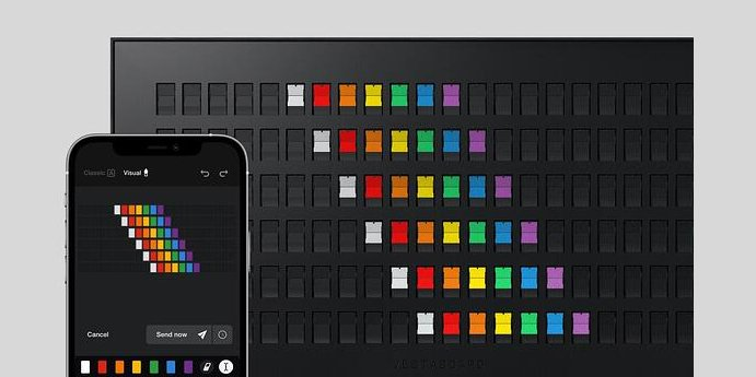 Vestaboard smart messaging display showing rainbow pattern and app visual editor