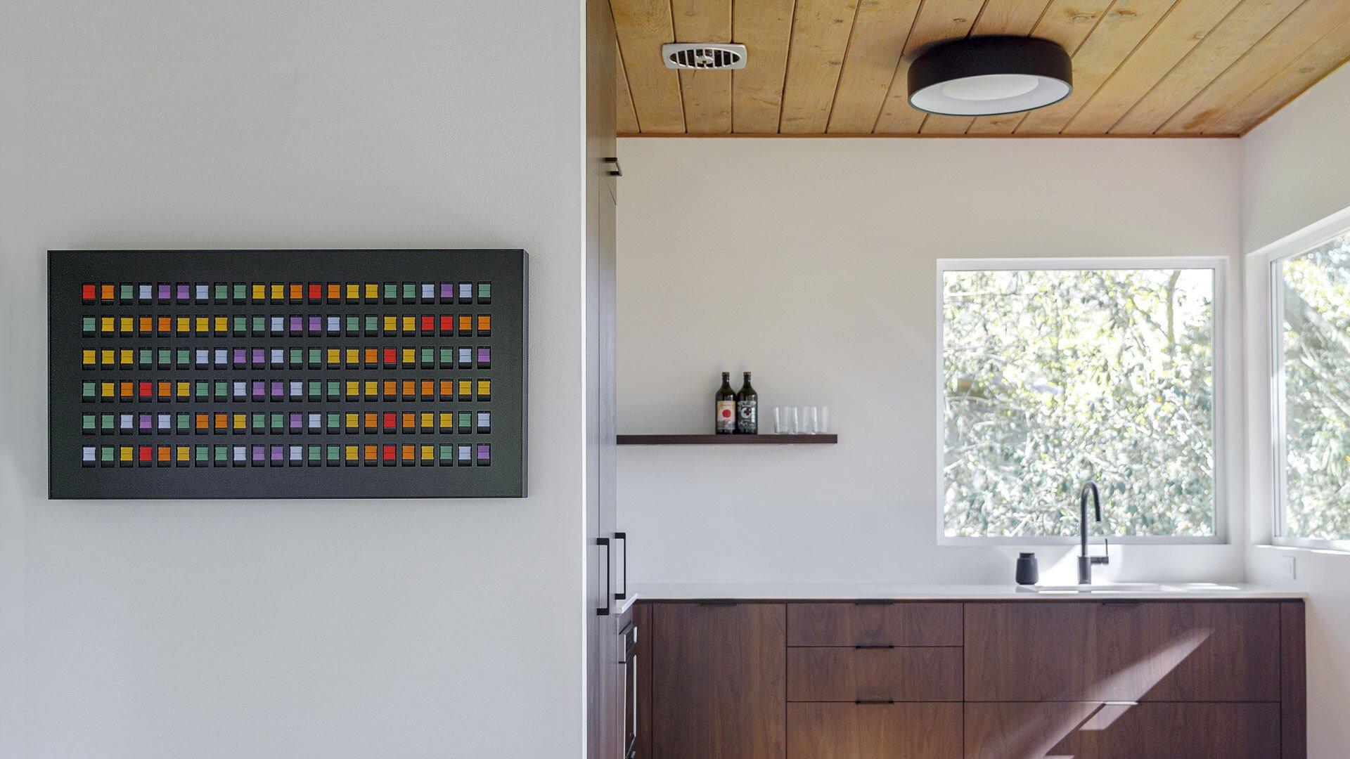 Vestaboard in home office displays a colorful pattern